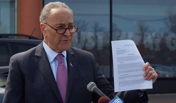 Sen. Chuck Schumer holds a petition as he calls
