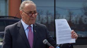 Sen. ChuckSchumer holds a petition as he calls