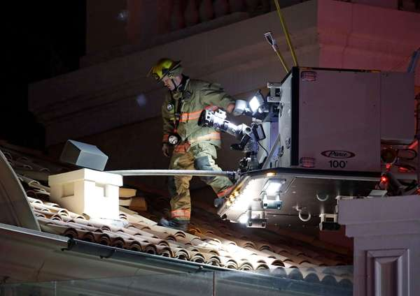 A firefighter walks onto the roof near the