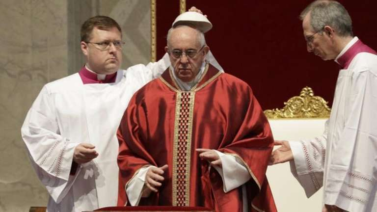 Pope Francis is helped to wear his skullcap