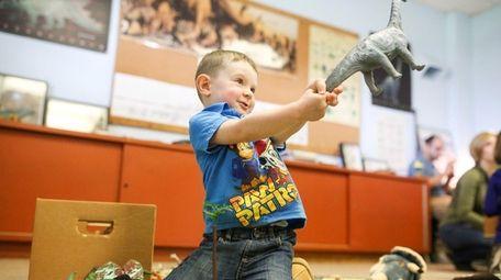 James Hall of Bayside, 2, plays with dinosaur