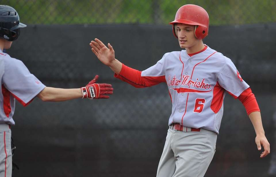 Alec Maag, Center Moriches catcher, right, gets congratulated