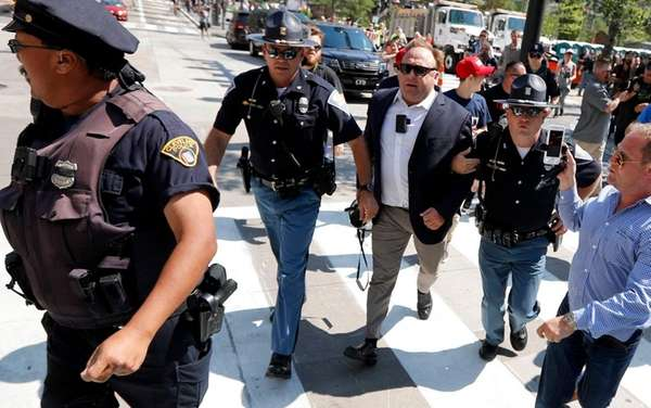 Alex Jones, center right, is escorted by