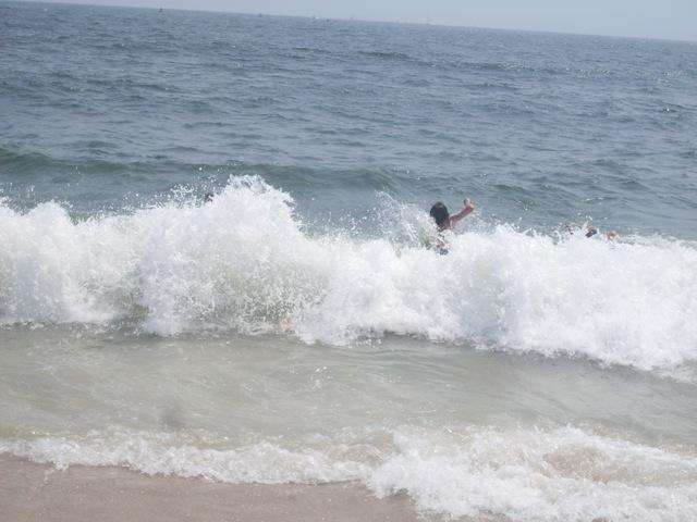 Swimmers jump over the waves.