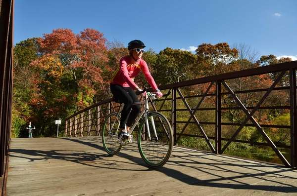 A cyclist rides over a small bridge on