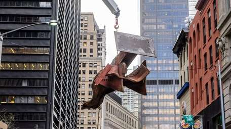 Iron workers remove a steel beam, recovered from
