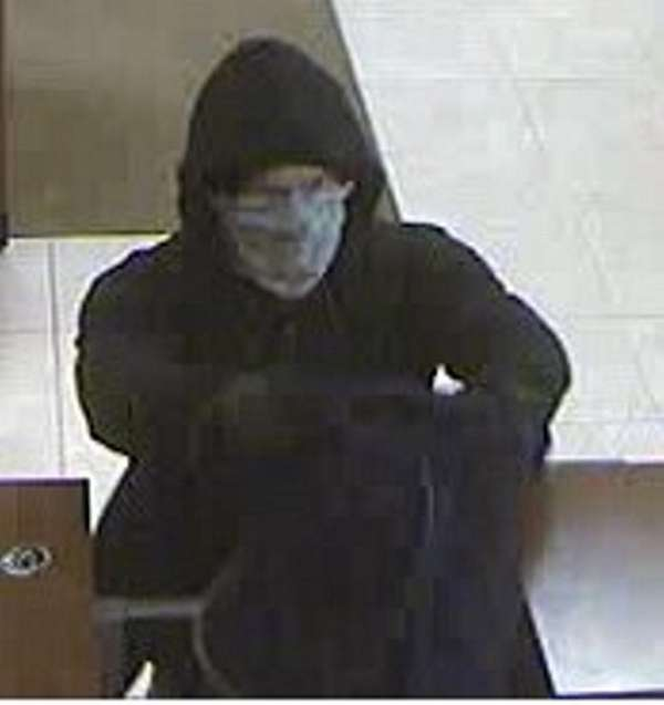 A hooded man wearing a bandanna over his