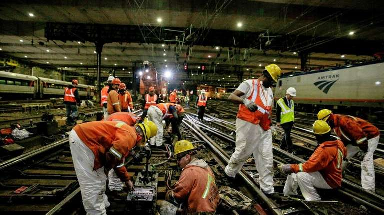Amtrak track workers wire a replacement switch