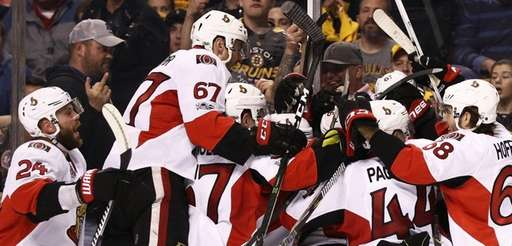 Members of the Ottawa Senators swarm Clarke MacArthur