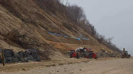 Workers shore up an area near Bluff Road