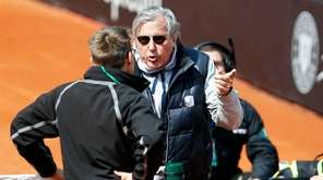 Romania's Fed Cup team captain Ilie Nastase, center, argues