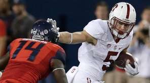 Stanford running back Christian McCaffrey (5) stiff-arms Arizona