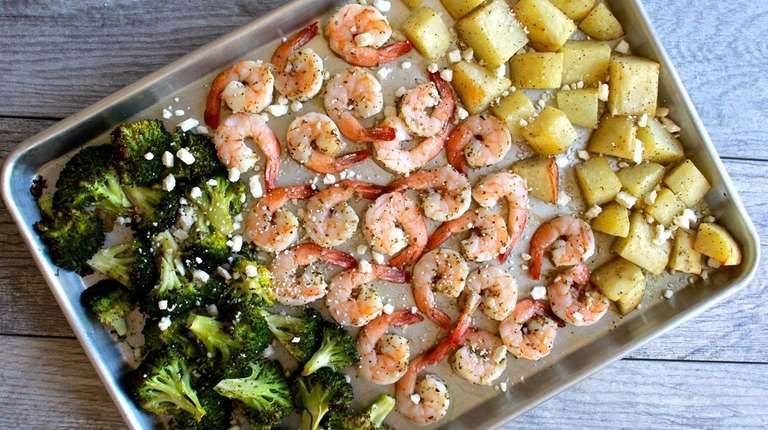 Shrimp, potatoes and broccoli are roasted on a