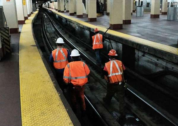 Maintenance workers walk along tracks used by NJ