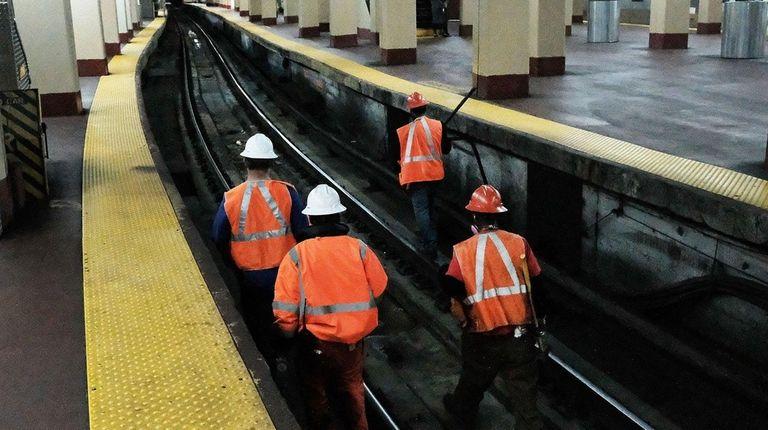 Maintenance workers walk along tracks used by NJ
