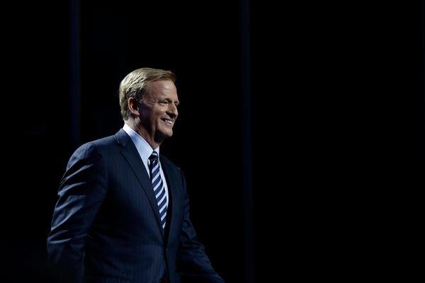 NFL Commissioner Roger Goodell smiles as he walks