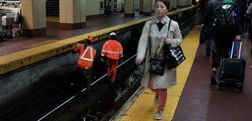 Track maintenance workers walk along train tracks used