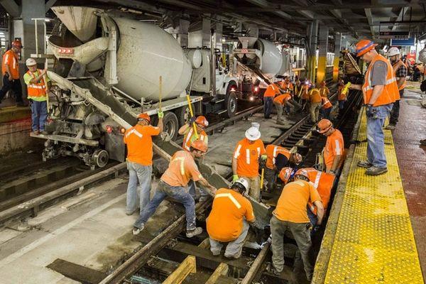 Amtrak crews pour concrete onto Track 7 of