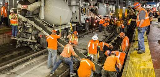 Amtrak crews pour concrete onto Track 7 of
