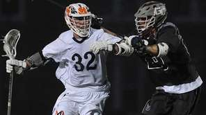 Steven Schneider #32 of Manhasset, left, gets pressured