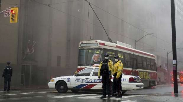Police block the street as smoke pours into