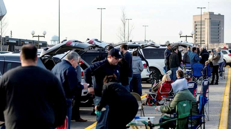Concertgoers tailgate in the parking lot ahead of