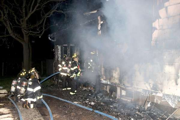 Firefighters battle a house fire on Seamans Neck