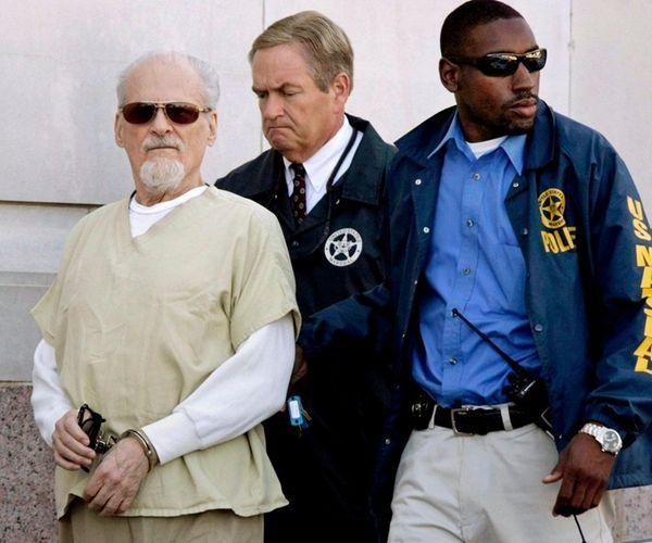 Tony Alamo, left, is escorted to a waiting