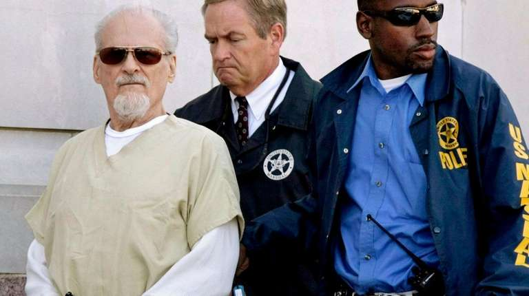 Tony Alamo, left, is escorted to a waiting