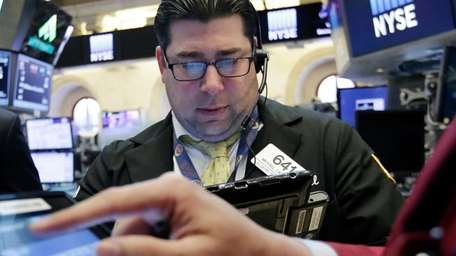 Trader Michael Capolino, left, works on the floor