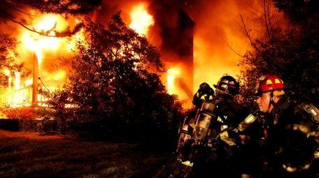 Firefighters battle a house fire on Sunrise Lane