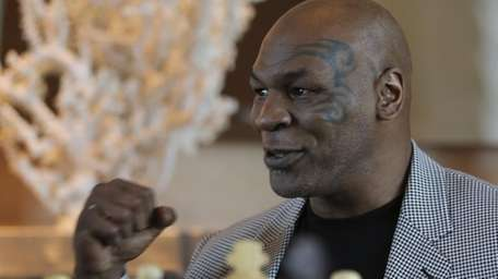 Mike Tyson makes a fist during an interview