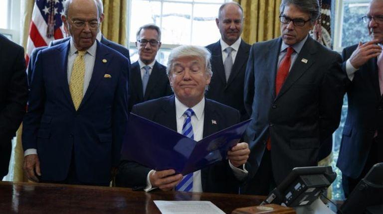 President Donald Trump, flanked by Commerce Secretary Wilbur