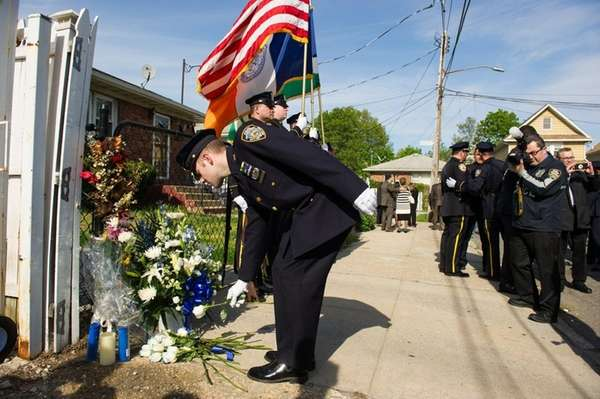 Officers lay flowers after the ceremony. Police hold