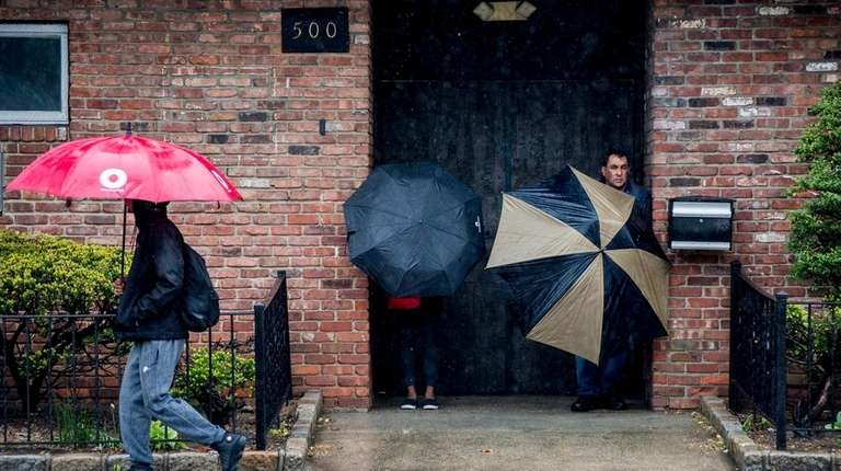 Pedestrians take shelter on Friday, May 5, 2017,