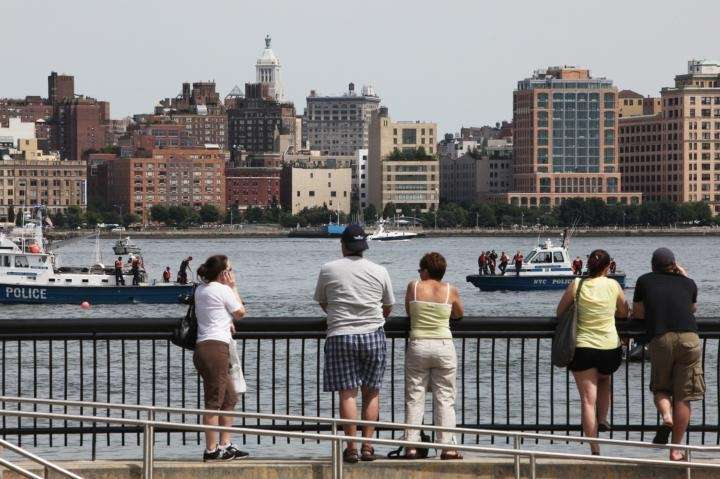 People watch as rescue boats search the area