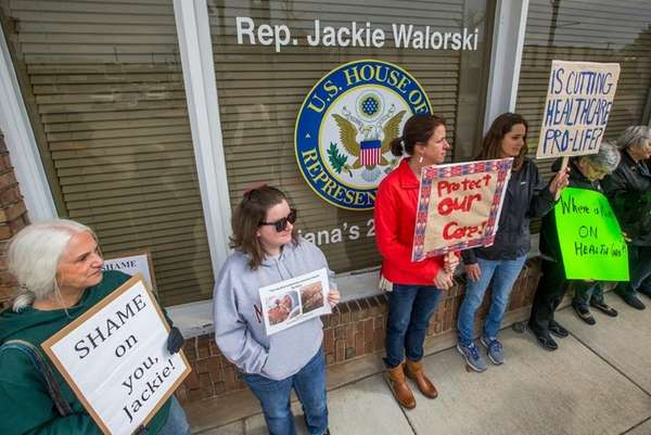 Demonstrators hold signs to protest Rep. Jackie Walorski's,