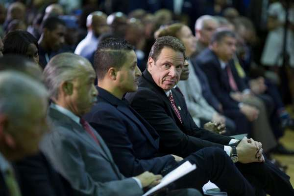 Gov. Andrew M. Cuomo sits next to Akeem