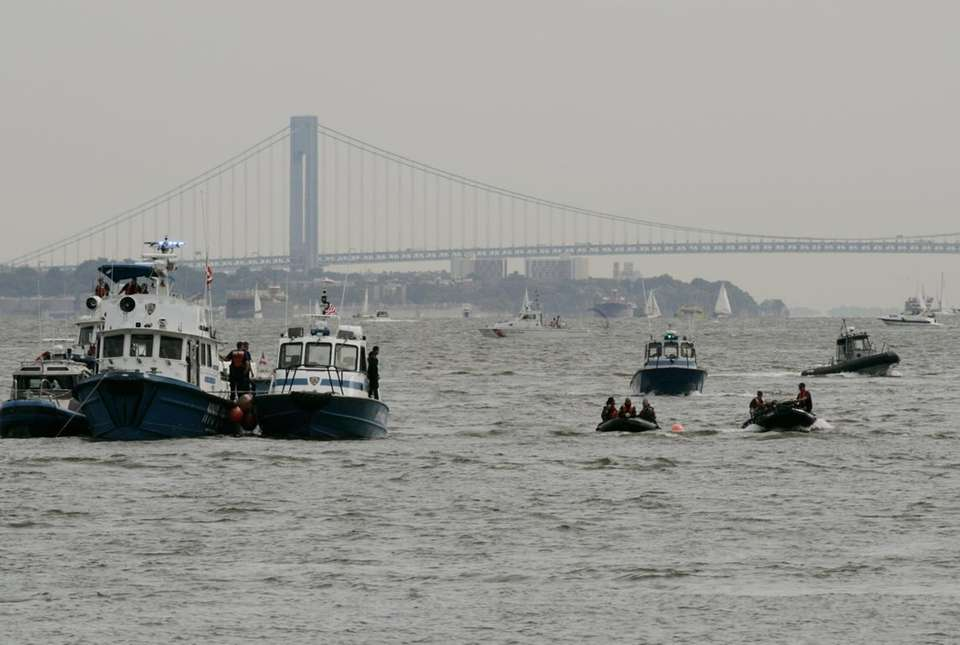 Small police boats, right, sit at an orange