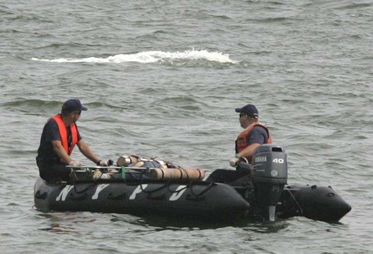 Police officers transport a body in the Hudson