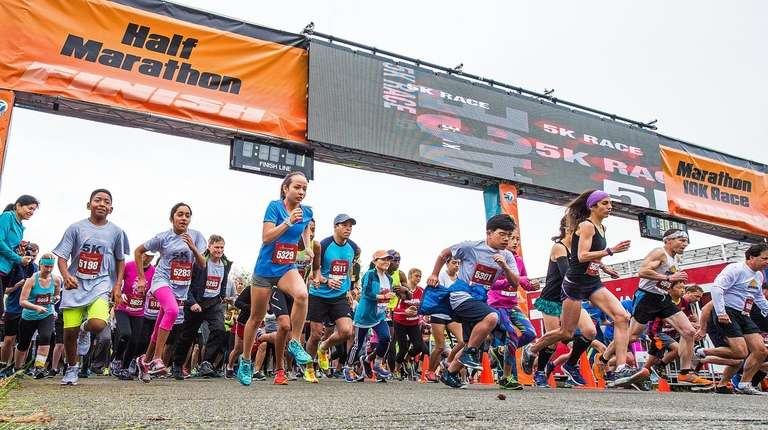 Runners charge through the starting gate of the