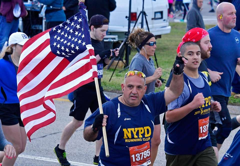 A runner carrying the American Flag runs the