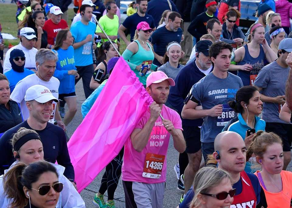 A man carrying a pink flag in honor