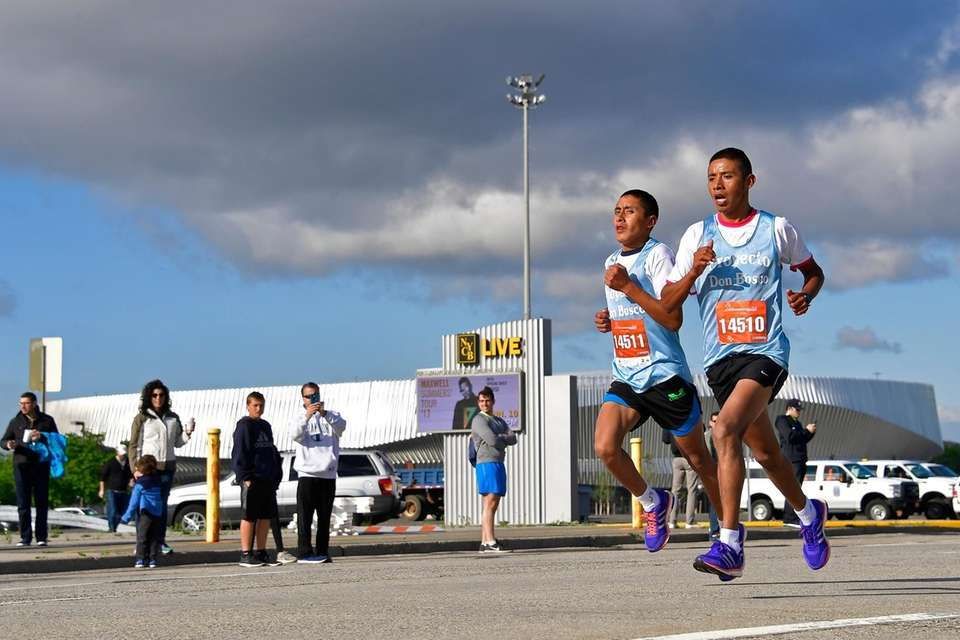 Half-marathon participants run past the renovated Nassau Coliseum
