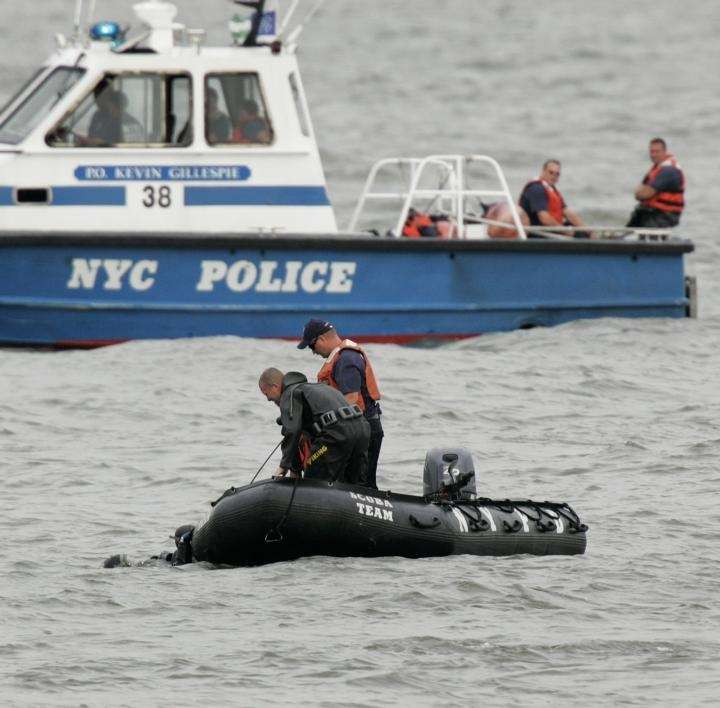Police divers are seen near a small boat