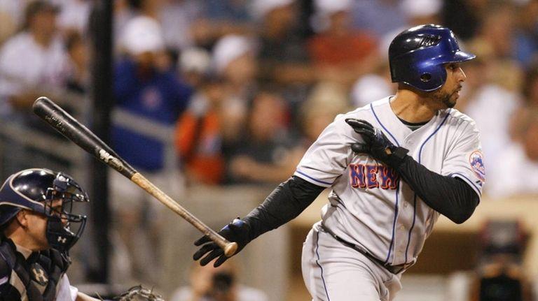 New York Mets' Alex Cora, right, follows through