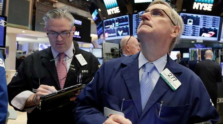 Trader Christopher Fuchs, right, works on the floor