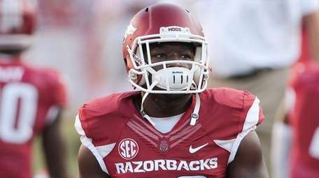 Arkansas running back Rawleigh Williams III stretches before