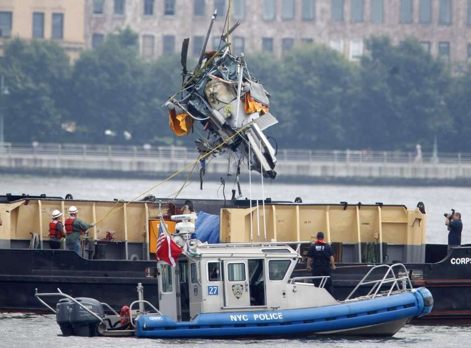 The wreckage of a helicopter is lifted by