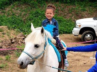 Karina Tindal, 3, beams as she rides a